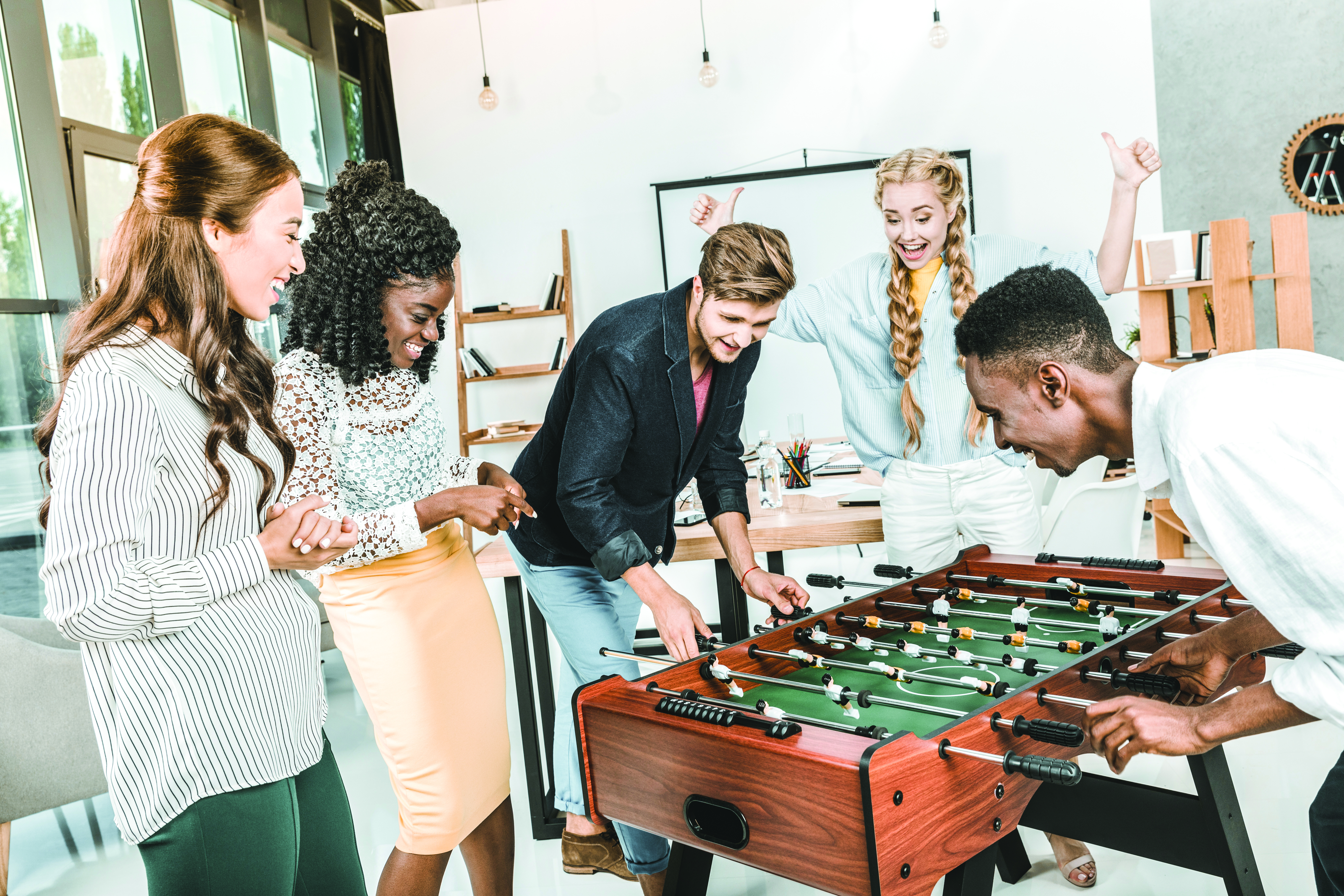 A group of younger guests enjoy playing games like table football in modern hotel lobbies.
